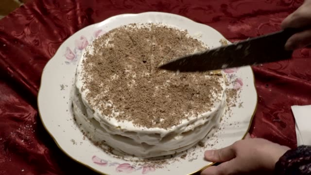 eine frau schneidet in gleiche stücke einen festlichen weißen kuchen mit geriebener schokolade auf der oberseite verziert. kuchen ist auf einem weißen teller und roten tischdecken wert. nahaufnahme. der blick von oben. 4k. - scheibe portion stock-videos und b-roll-filmmaterial