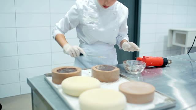 vidéos et rushes de femme coupe des résidus de crème excédentaires. - boulanger