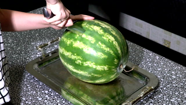 Woman cuts watermelon in slices with knife. video