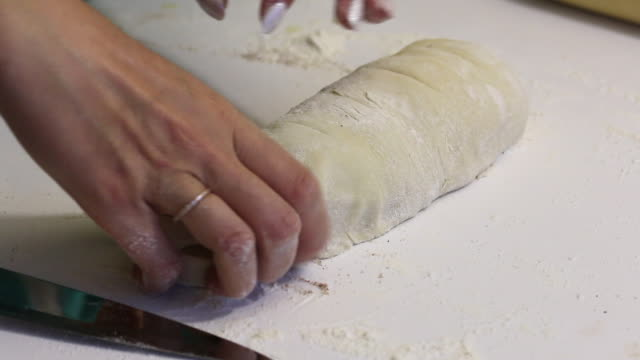 a woman cuts with a knife rolled into a roll dough for cinnabons. nearby are cooking tools. - formare pane video stock e b–roll