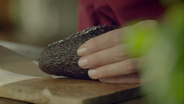Woman cutting avocado Close-up shot of a woman cutting an avocado on a cutting board. avocado stock videos & royalty-free footage