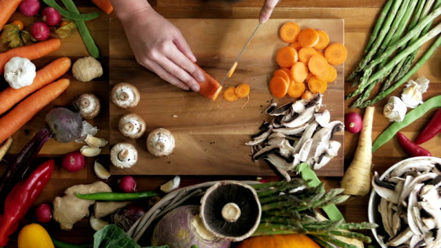 vídeos de stock e filmes b-roll de woman cutting carrot on wooden board in kitchen - vegetables