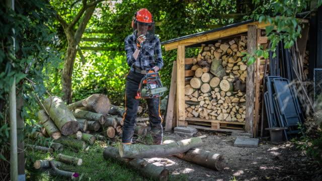 frau schneidet brennholz mit einer kettensäge - brennholz stock-videos und b-roll-filmmaterial