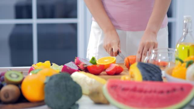 frau schneiden von früchten in der küche zu einem fruchtcocktail. - obst stock-videos und b-roll-filmmaterial