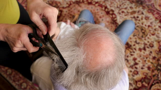 Woman cutting her husband's hair at living room during isolation period High angle view of woman cutting her husband's hair at living room during isolation period wearing a towel stock videos & royalty-free footage