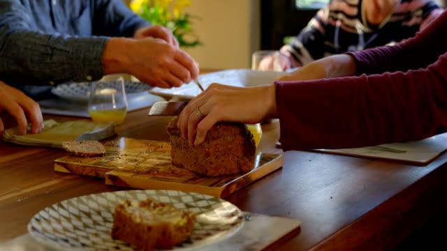 kvinnan skära limpa bröd på matbord 4k - brödlimpa bildbanksvideor och videomaterial från bakom kulisserna