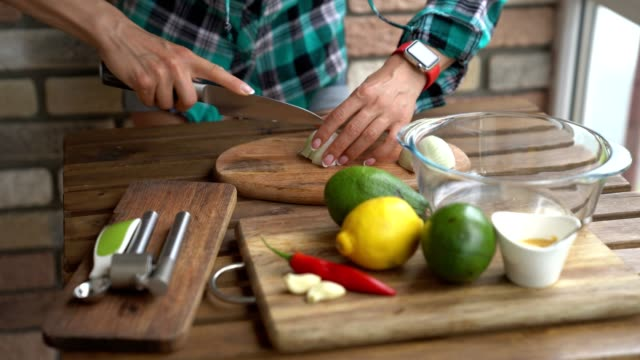 Woman cutting onion for guacamole recipe in kitchen Woman cutting onion for guacamole recipe in kitchen. dipping sauce stock videos & royalty-free footage