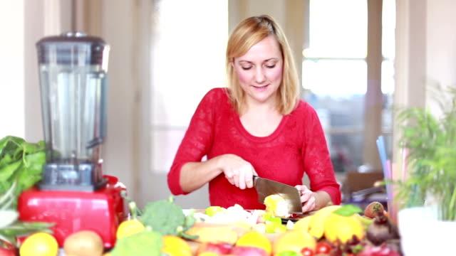 Woman cutting orange for fruit shake video