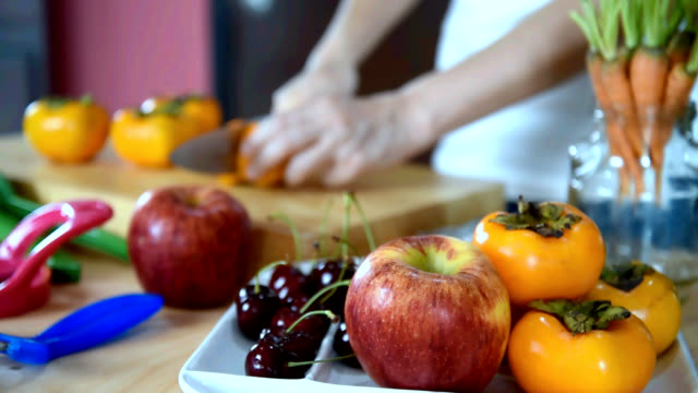 Woman cutting persimmon, variety fruits in kitchen/ healthy lifestyle conceptual Blurred motion of woman's hands cutting persimmon, variety fruits in colorful modern kitchen / healthy lifestyle conceptual pantry stock videos & royalty-free footage