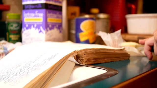 vidéos et rushes de femme, découpage beurre lors de la lecture d'un vieux livre livre de cuisine ou de la recette de cuisine - recette
