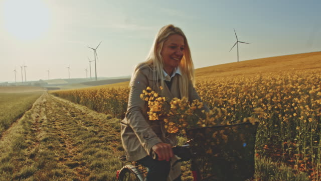 SLO MO Woman cycling along field of canola with wind turbines in the distance video