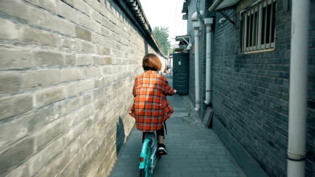 Woman cycling in Hutong(lane),Beijing,China. Woman cycling in Hutong(lane),Beijing,China. plaid stock videos & royalty-free footage
