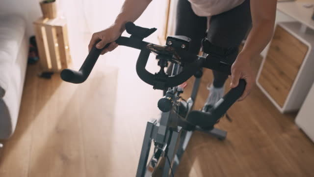 SLO MO Woman cycling on the exercise bike Slow motion medium shot of an unrecognizable woman cycling on the exercise bike at home. Conceptual shot of the self isolation time. Shoot in 8K resolution. exercise bike stock videos & royalty-free footage