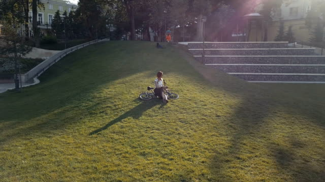 woman cyclist lying on green grass in park and using mobile phone - ragazza auricolari rossi video stock e b–roll