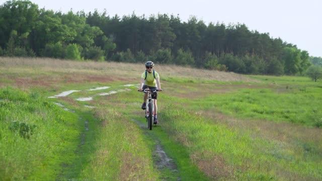 radfahrerin fährt auf dem fahrrad auf senderwegn - kopfbedeckung stock-videos und b-roll-filmmaterial