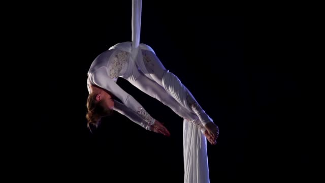 woman dancer on aerial silk, aerial contortion, aerial ribbons, aerial fabric in posing exercise. slow motion - circus стоковые видео и кадры b-roll