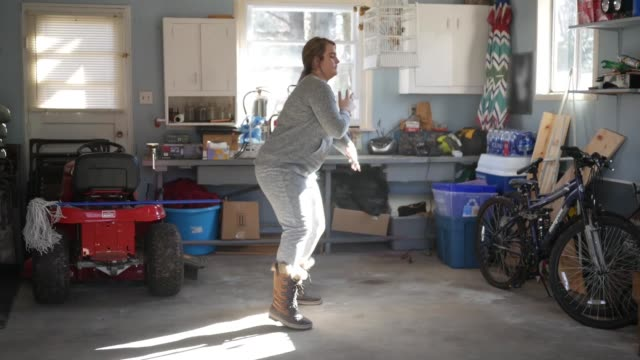Woman dances in a garage to music after spring cleaning Woman dances in a garage to music after spring cleaning chance stock videos & royalty-free footage