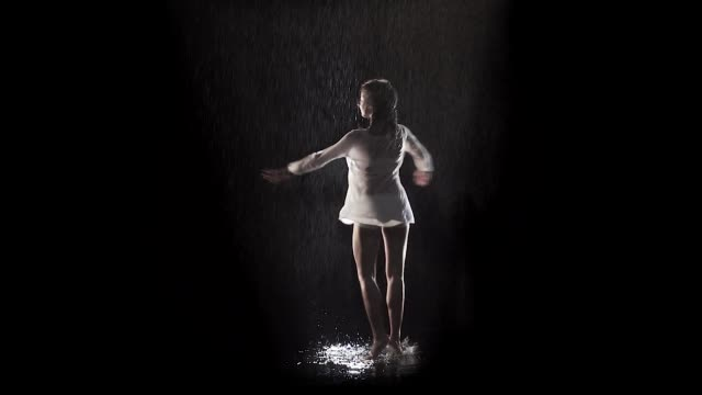 woman dancing and rotating under the rain with black background and backlight - video