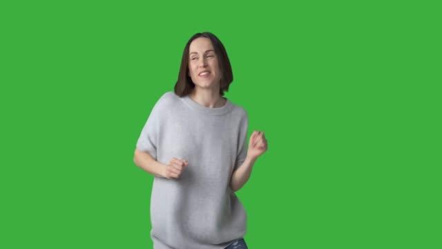 woman dancing and singing over green background - krótkie włosy filmów i materiałów b-roll