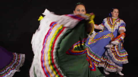 Woman dancing and twirling dresses Slow motion shot of women in traditional Mexican dress dancing on black background cultures stock videos & royalty-free footage
