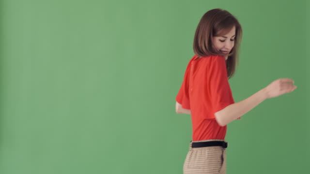 woman dancing backwards over green background - comparsa video stock e b–roll
