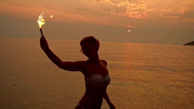 Mujer bailando de San Luis Obispo Missouri con bengala en la playa - vídeo