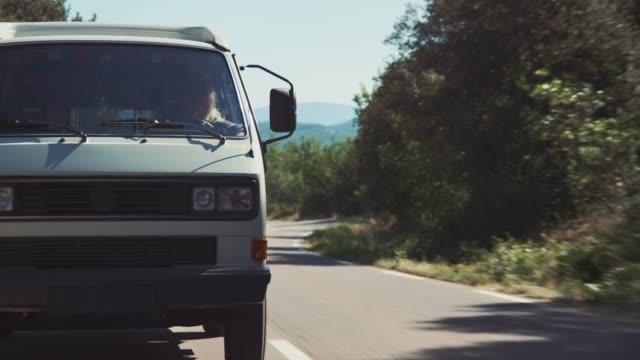 woman dangling legs from van window during trip - furgone video stock e b–roll