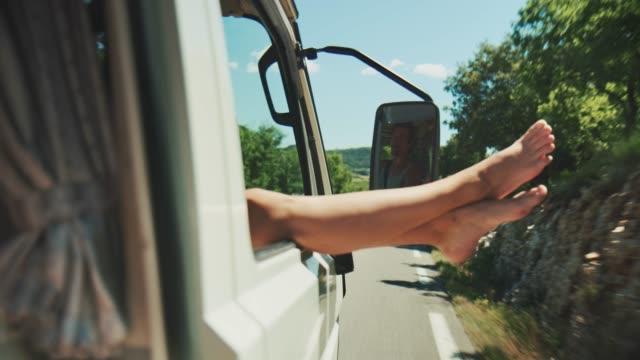 Woman dangling legs through window during journey