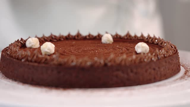 vídeos de stock e filmes b-roll de woman decorates chocolate tart with white candies on table - bolo rainha
