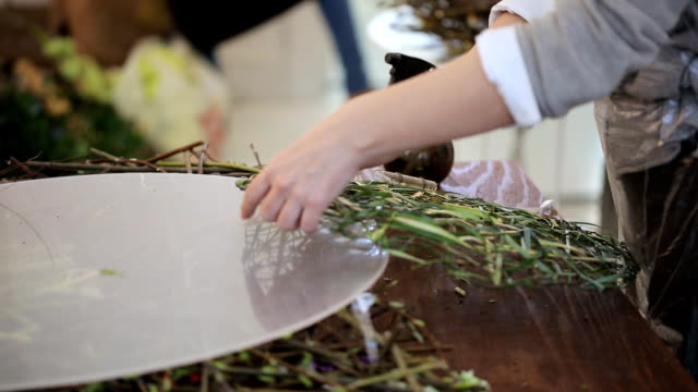 Woman decorates wreath, made from grass, with glass flasks video