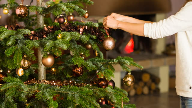 Woman decorating christmas tree Woman hanging an ornament onto christmas tree with fireplace burning in the background hanging stock videos & royalty-free footage