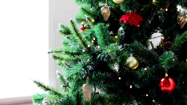 woman decorating christmas tree with ball video