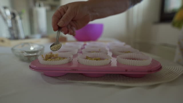 Woman decorating her salty cupcakes with sesame Senior woman sprinkling sesame seeds on her corn bread mixture sesame stock videos & royalty-free footage