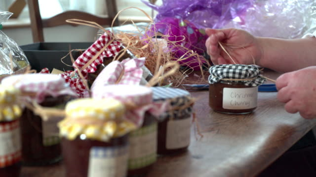 Woman decorating homemade Christmas gift preserves. Womans hands wrapping Christmas​ presents jar stock videos & royalty-free footage