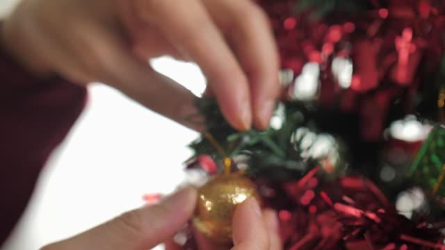 woman decorating the christmas tree with ball ornament - jodła filmów i materiałów b-roll