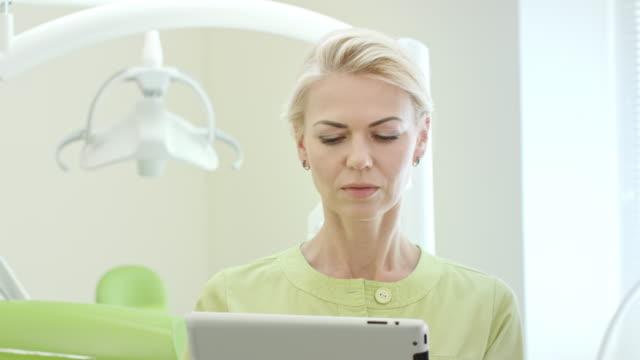 女性歯科医がタブレット コンピューターを使用して。タブレット pc を使用して歯科の専門家 - 歯科点の映像素材/bロール