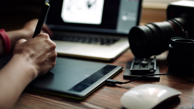 vídeos de stock e filmes b-roll de woman designer working at a laptop with a graphics tablet. - design