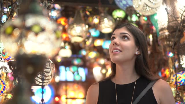 Woman discovering Lighted Chandeliers at a Bazar