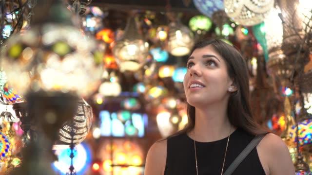 donna alla scoperta di lampadari illuminati in un bazar - grand bazaar video stock e b–roll