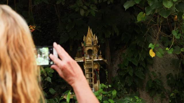 vidéos et rushes de femme découvre sanctuaire bouddhiste en forêt - évasion du réel