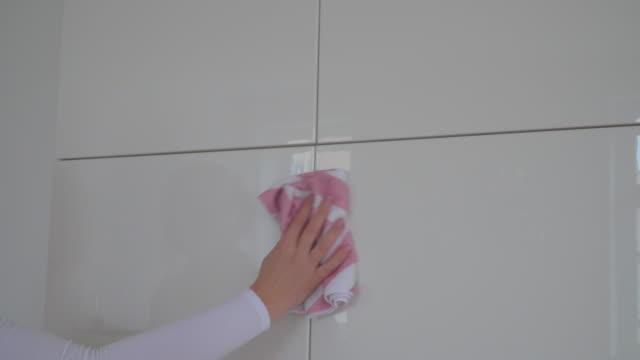 Woman disinfect  ceramic tiles in bathroom