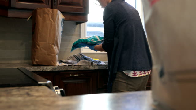 woman disinfecting groceries, fruits and vegetables during covid-19 crisis at home - grocery home video stock e b–roll