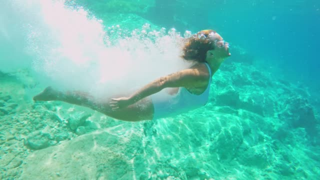 ms woman diving into sunny blue ocean - tuffarsi video stock e b–roll
