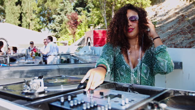 Woman DJing at Pool Party A woman spins records and dances at a daytime party in a backyard. She is wearing a green sequinned dress. pool party stock videos & royalty-free footage