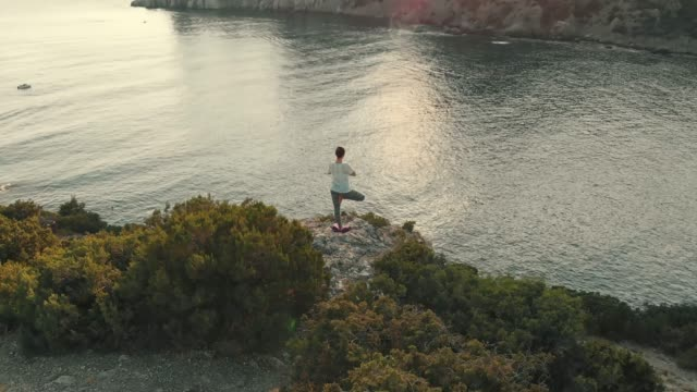 vídeos y material grabado en eventos de stock de mujer hacer yoga al atardecer vista aérea - posición descriptiva