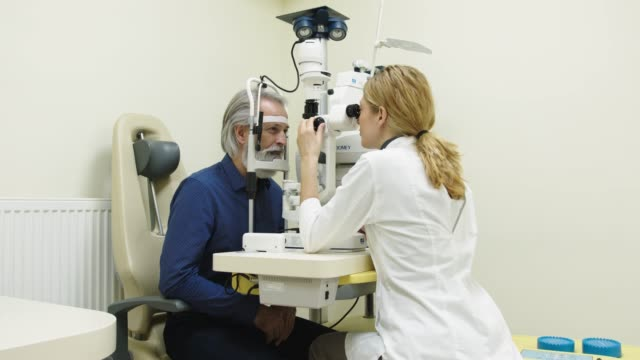 Woman doctor examining a senior patient in ophthalmology clinic video