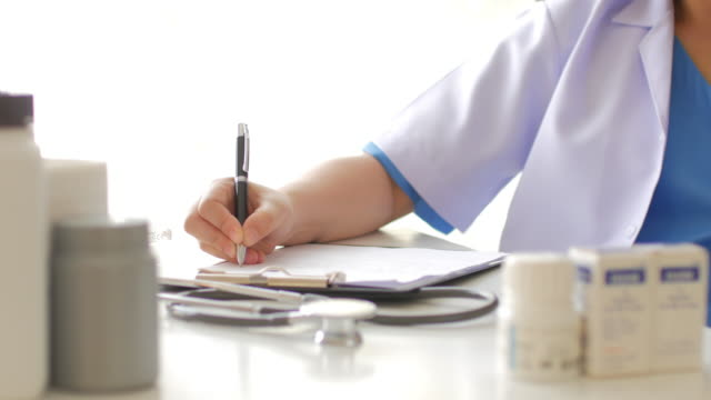 Woman doctor filling on clipboard at her desk video
