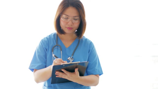 Woman Doctor filling writing on clipboard chart with blue uniform video