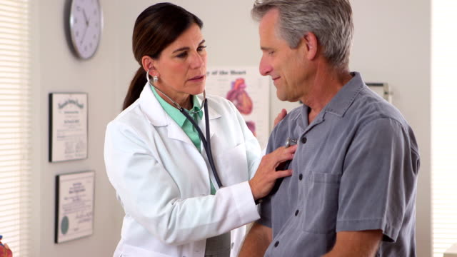Woman doctor listening to elderly patient's heartbeat video