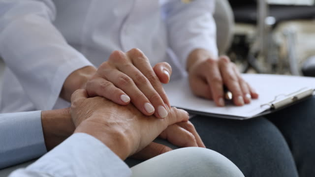 Woman doctor nurse holding hand of elderly grandma patient, closeup Young woman doctor nurse hold hand of elderly female grandma patient at home hospital visit give support help and comfort concept, medical care responsibility, senior people healthcare, close up view oncology stock videos & royalty-free footage